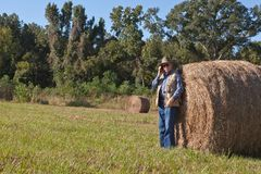 Mature man and hay stack Stock Images