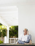Mature Man With Headphones On Verandah Royalty Free Stock Image
