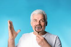 Mature man with healthy teeth and magnifier. On color background stock photos