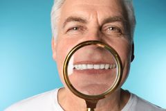 Mature man with healthy teeth and magnifier on color background. Closeup stock image
