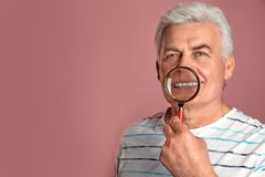 Mature man with healthy teeth and magnifier. On color background. Space for text stock photography