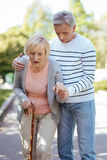 Mature man helping his aged mother in the park. Always supporting my mother. Involved caring mature men caring about his old mother and helping her to make steps Stock Photo