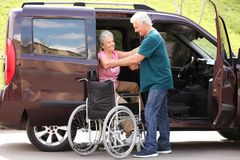 Free Mature Man Helping Senior Woman To Get Out From Van Into Wheelchair Stock Photos - 159893483