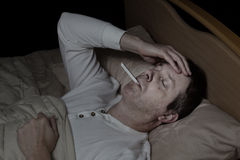 Mature man with high fever in bed Royalty Free Stock Photography