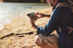 Mature man on hike using a tab for navigation Stock Photos