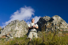Mature man hiking on mountain trail, leaning on hiking pole, admiring scenery, smiling, low angle view stock images