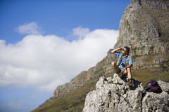 Mature man hiking on mountain trail, sitting on rock, looking at scenery, shielding eyes, side view royalty free stock photos