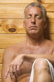 A mature man with his eyes closed in a sauna. Close-up of a mature man with his eyes closed in a sauna stock images