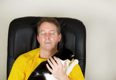 Mature man and his family cat relaxing in a massage chair Stock Photo