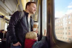 Mature man and his little son looks out the window of the car in the subway in new York stock photos