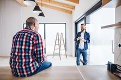 A mature man with his senior father furnishing new house, a new home concept. A portrait of mature men with his senior father drinking coffee when furnishing royalty free stock images