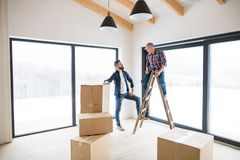 A mature man with his senior father furnishing new house, a new home concept. A mature men with his senior father furnishing new house, a new home concept. Copy royalty free stock photography