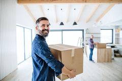 A mature man with his senior father furnishing new house, a new home concept. A portrait of mature men with his senior father furnishing new house, a new home stock photography