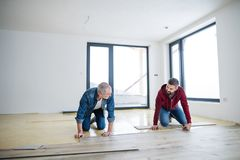 A mature man with his senior father laying wood flooring, a new home concept. A front view of mature men with his senior father laying wood flooring, a new home royalty free stock image