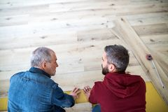 A mature man with his senior father laying wood flooring, a new home concept. A rear and top view of mature men with his senior father laying wood flooring, a stock image