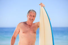 Mature man with his surfboard Royalty Free Stock Images