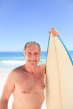 Mature man with his surfboard. Looking the camera Stock Photos