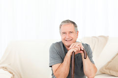 Mature man with his walking stick on his bed Royalty Free Stock Photo
