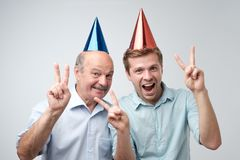 Mature man and his young son celebrating happy birthday wearing funny caps. Mature men and his young son celebrating happy birthday wearing funny caps stock images
