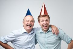 Mature man and his young son celebrating happy birthday wearing funny caps. stock image