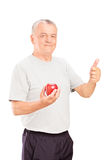 Mature man holding an apple and giving thumb up Royalty Free Stock Photo
