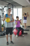 Mature man holding ball in the gym, people exercising on the background Royalty Free Stock Image
