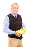 Mature man holding bananas Stock Photography