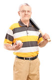 Mature man holding a baseball bat and ball Stock Photos