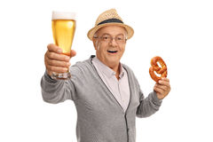 Mature man holding beer and pretzel. Mature man holding a pint of beer and a pretzel isolated on white background stock photo