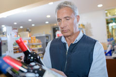 Mature man holding bottle red wine stock photos