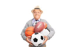 Mature man holding bunch of different balls Stock Photography