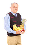 Mature man holding bunch of fruit in his hands Stock Photo