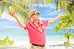 Mature man holding a cocktail and gesturing joy Royalty Free Stock Images
