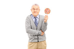 Mature man holding a colorful lollipop. Isolated on white background stock image
