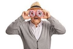 Mature man holding donuts in front of his eyes royalty free stock photos