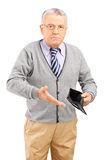 Mature man holding an empty wallet Royalty Free Stock Photo