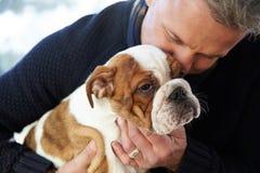 Mature Man Holding English Bulldog Puppy Royalty Free Stock Photos