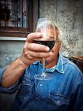 Mature man holding glass of red wine Royalty Free Stock Photo
