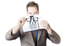 Mature Man Holding Glasses And Eye Checking Chart Royalty Free Stock Images
