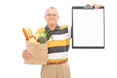 Mature man holding grocery bag and a clipboard Royalty Free Stock Image
