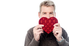 Mature man holding heart shaped gift box Stock Photo