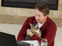 Mature man holding his family pet while working at home. Photo of mature man reading computer screen, with family cat in his lap, while working from home with royalty free stock photos