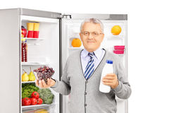 Mature man holding a milk bottle and bowl of grapes next to a fr. Smiling mature man holding a milk bottle and bowl of grapes next to a refrigerator isolated on Royalty Free Stock Images