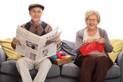 Mature man holding newspaper and mature woman knitting sitting o Royalty Free Stock Photo