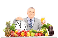 Mature man holding an orange juice with clock, fruit. And vegetables on a table on white background stock photos