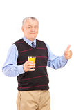 Mature man holding an orange juice and giving thumb up Royalty Free Stock Images