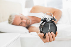 Mature man holding out alarm clock in bed Stock Images