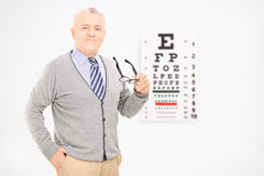 Mature man holding a pair of glasses in front of an eye chart. Mature man holding a pair of glasses in front of an eyesight test royalty free stock photo