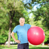 Mature man holding a pilates ball in park. Mature sporty man holding a pilates ball in park Stock Photo
