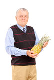 Mature man holding a pineapple Stock Photos